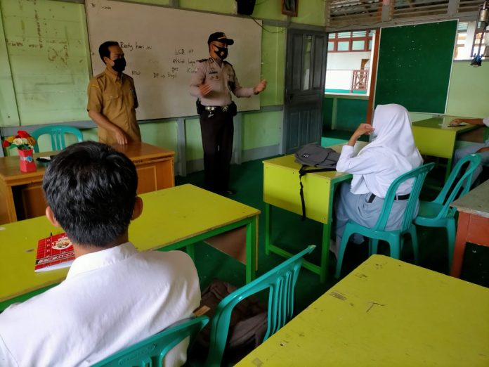 Kasatgas IV Rehabilitasi Ops Aman Nusa II Polres Sekadau saat berkunjung ke SMK Amaliyah edukasi prokes