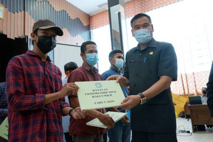 Ketua DPRD Kabupaten Kubu Raya saat menyerahkan bantuan sarana dan prasarana secara simbolis kepada perwakilan UMKM.
