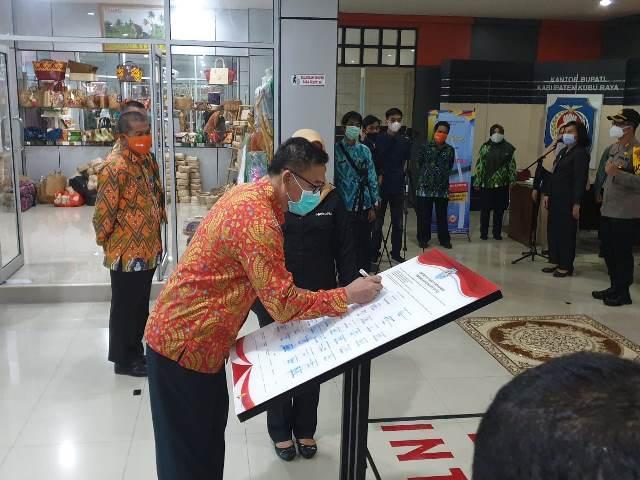 Ketua DPRD Kubu Raya Agus Sudarmansyah saat menanda tangani komitmen pencegahan korupsi.