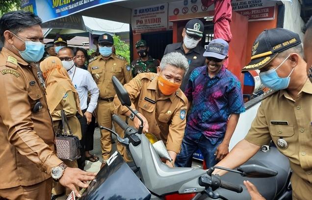 Bupati saat mengisi minyak salah satu motor bagian dari simbolis peresmian sub penyalur BBM di Desa Padang Tikar I Kecamatan Batu Ampar.