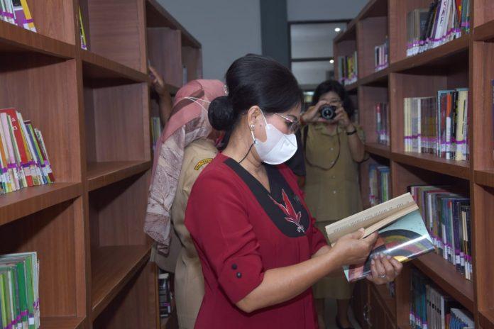 Pegiat literasi Sanggau yang juga ketua Dekranasda Sanggau saat melihat koleksi buku di Arpusda.
