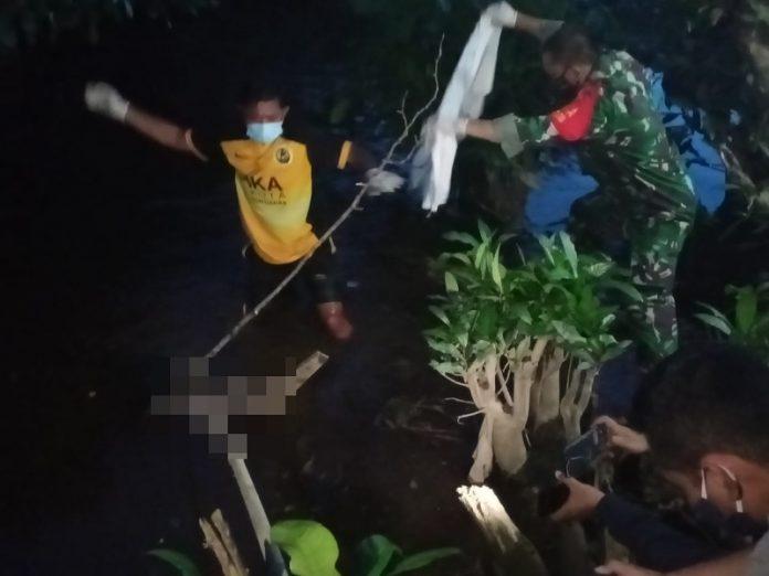 Petugas dibantu warga sedang mengangkat mayat bayi yang ditemukan mengapung di parit