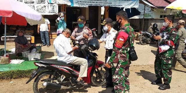 Camat Kapuas memberikan masker kepada masyarakat yang kedapatan tak bermasker saat berada di tempat umum.