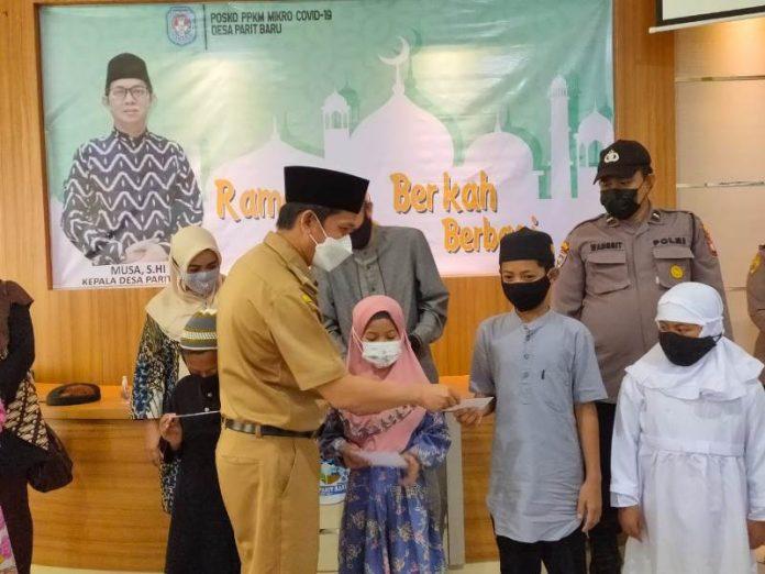 Kepala Desa Parit Baru memberikan santuan kepada anak yatim piatu.