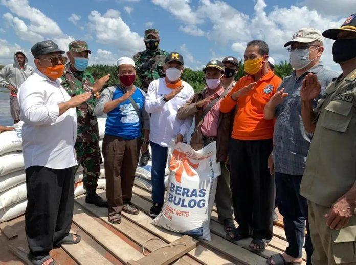 Bupati Kubu Raya saat menyerahkan bantuan beras untuk warga terdampak banjir di Kecamatan Kuala Mandor B.