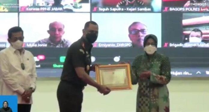 Kajari Sanggau Tengku Firdaus saat menerima penghargaan dari Mensos RI Tri Rismaharini.