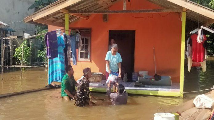 Personel POlres Melawi dan relawan GP Ansor menyalurkan bantuan kepada korban banjir.
