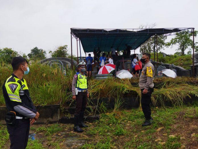 Personel kepolisian saat mengawal proses pemakaman pasien covid019 yang meninggal dunia