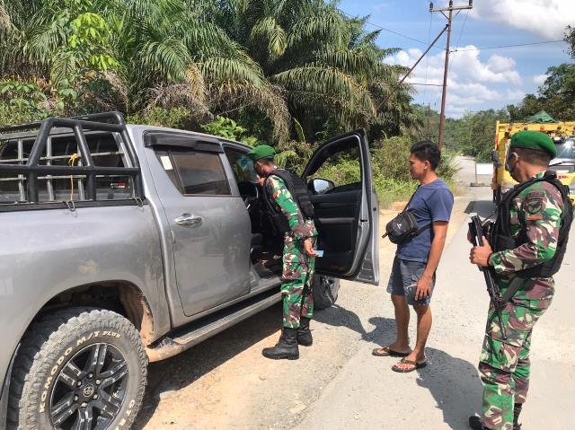 Anggota TNI Pos Koki Sui Daun saat melakukan pemeriksaan kendaraan yang melintas di Jalan Trans Kalimantan yang melewati Desa Malenggang.